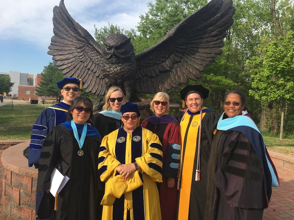 faculty members in their graduation gowns in front of the owl statue